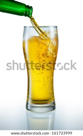 Beer is pouring into the glass - stock photo