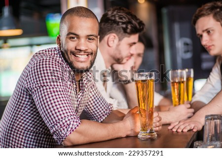 Beer is the best drink for men. Three other men drinking beer and having fun together in the bar until the bartender communicates with them