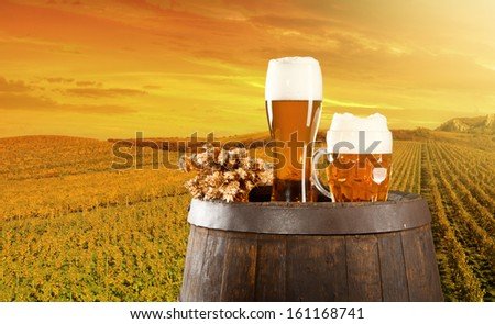 Beer keg with glasses of beer on rural countryside background - stock photo