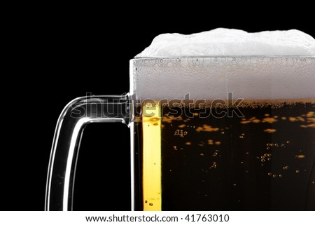 Beer mud with froth close-up isolated over the black background - stock photo