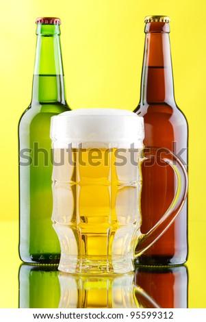 Beer mug and bottles on yellow background, studio photo - stock photo