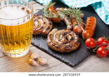 Beer mug and grilled sausages on wooden table - stock photo