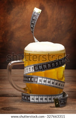 Beer mug and tape measure . Diet concept - stock photo