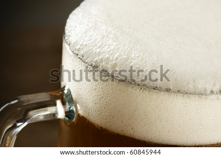 Beer mug with froth over dark background - stock photo