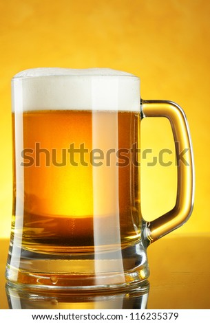 Beer mug with froth over yellow background