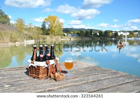 Beer on the wooden jetty against a lake - stock photo