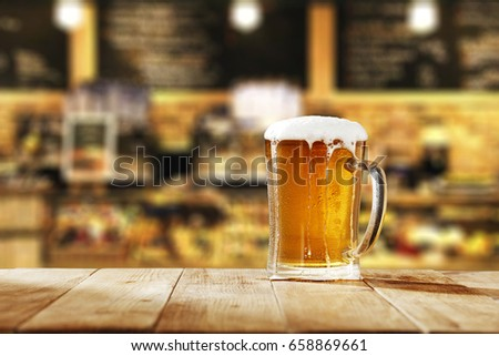 Beer on wooden table in bar and free space for your decoration
