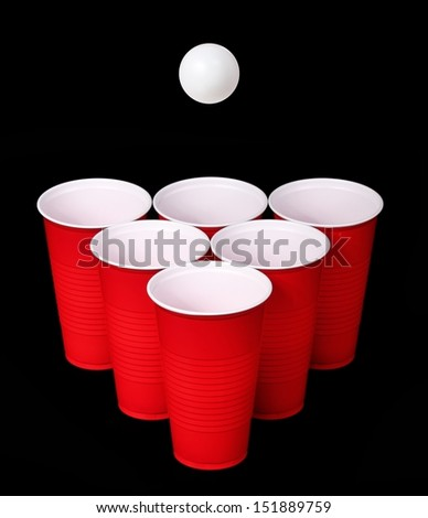 Beer pong. Red plastic cups and ping pong ball over black background - stock photo