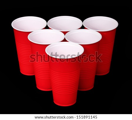 Beer pong. Red plastic cups over black background - stock photo