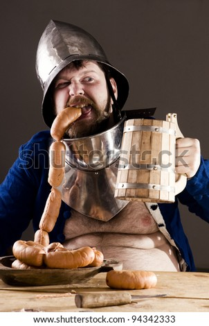 Beer! Portrait of expressive medieval warrior eating sausages. - stock photo