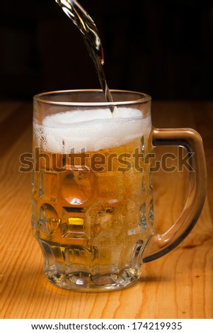 Beer poured into a glass on a wooden table. - stock photo
