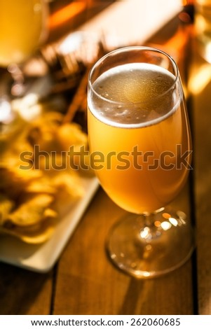 Beer. pouring beer with chicken wings in background.  - stock photo