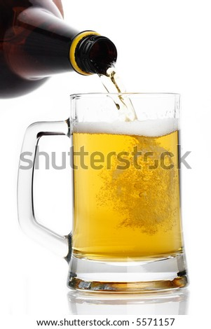 Beer pouring down into a mug isolated on white