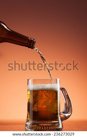 Beer pouring from bottle into glass  - stock photo