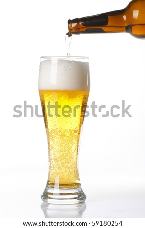 Beer pouring from bottle into glass isolated on white - stock photo