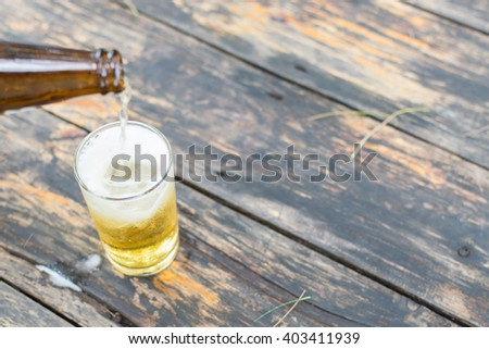 Beer pouring in glass with ice and froth on a wood table - stock photo