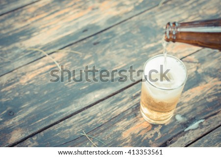 Beer pouring in glass with ice and froth on a wood table , process in vintage style - stock photo