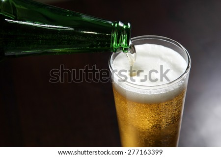 Beer pouring in the glass - stock photo