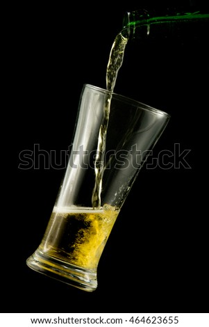 Beer pouring into a glass. Isolated on black background.