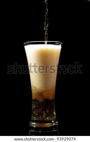 Beer pouring into glass on a black background