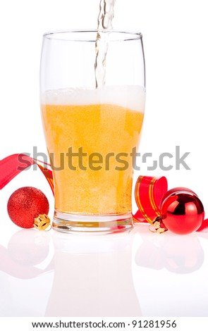 Beer pouring into glass, Red ribbon and Christmas Balls isolated on white background - stock photo