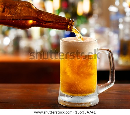beer pouring into mug in a bar - stock photo