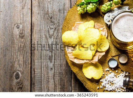 Beer rustic style . Beer and chips on a wooden background.