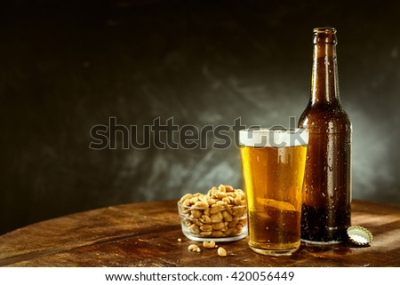 Beer served from a brown bottle into a long glass and a bowl of roasted salted peanuts on an old wooden bar table with copy space on slate behind - stock photo