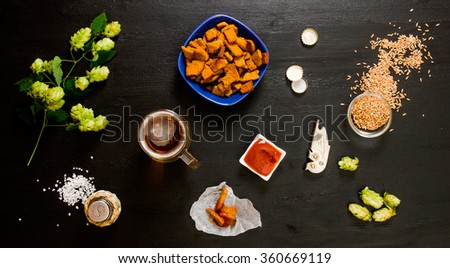 Beer set. A glass of beer, crackers, ketchup, salt. The ingredients for brewing: malt and hops. On a wooden black background. Top view - stock photo