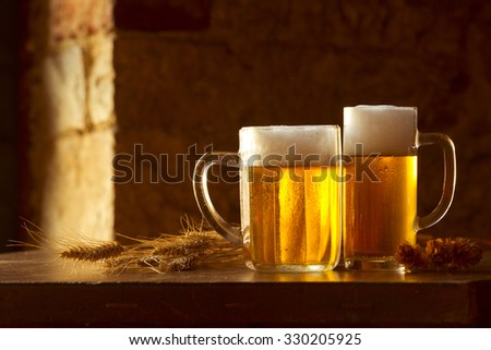 beer still life on the table with grain and hops - stock photo