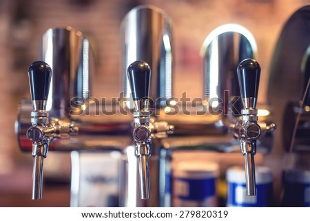 Beer tap at restaurant, bar or pub. Close-up details of beer draft taps in a row  - stock photo