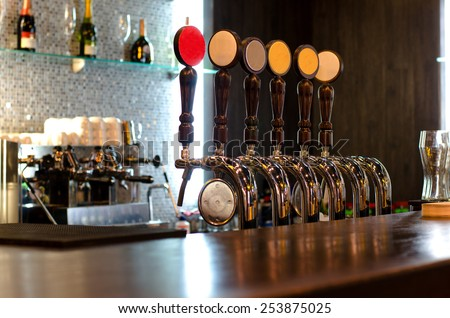 Beer taps behind a deserted bar counter for dispensing draft beer from a large storage keg below the wooden counter - stock photo