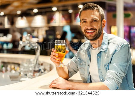 Beer time. Cheerful young man holding glass of beer and looking at camera while sitting at the bar counter - stock photo