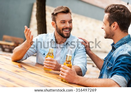 Beer time. Two cheerful young men talking to each other and holding bottles with beer while standing outdoors - stock photo