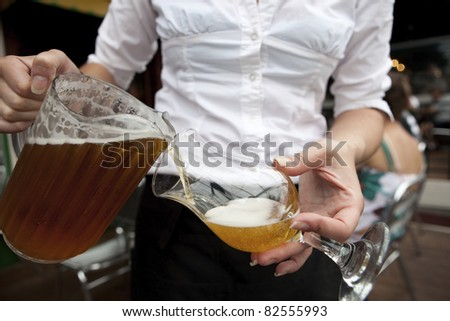 Beer Waitress Bar Maid pouring draught beer from a pitcher - stock photo