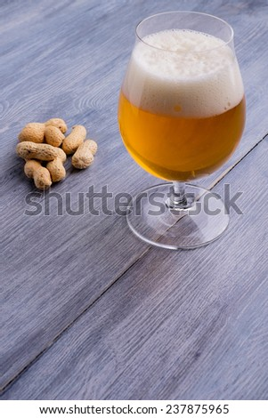 Beer with foam and peanuts on the side - stock photo