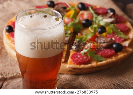 beer with foam close-up on background pizza on the table. horizontal  - stock photo