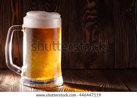Beer with foam. Cold beer in glass on a dark background. On the glass condensate.