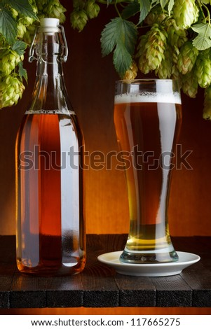 Beer with hop on wooden table still life - stock photo
