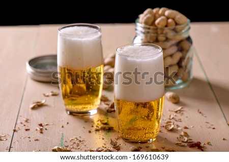 Beer with peanuts on old wood table - stock photo