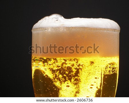 Beer within mug with foam over black background