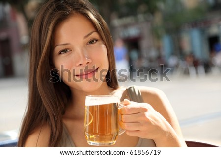 Beer woman enjoying a fresh draft beer outside on sidewalk cafe. Beautiful Caucasian / Asian model. - stock photo