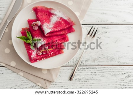 beet pancakes with powdered sugar and berries on wooden background. - stock photo