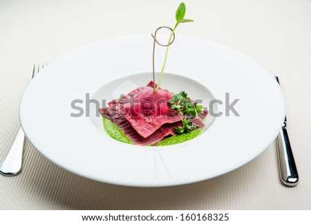 Beet ravioli with goat cheese, ricotta and mint filling - stock photo