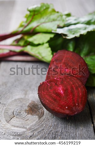 beet roots and green leaves on wooden background. shallow dof - stock photo