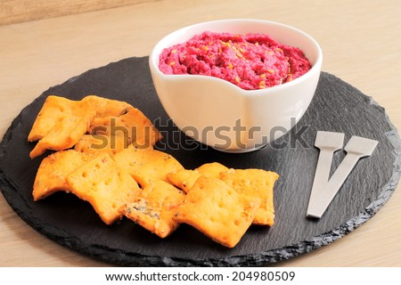 Beetroot and chickpea hummus with crackers - stock photo