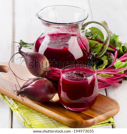 Beetroot  juice and bunch of fresh beetroots with leaves. Selective focus - stock photo