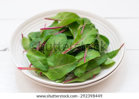 Beetroot leaves served on a white plate  on the  wooden boards