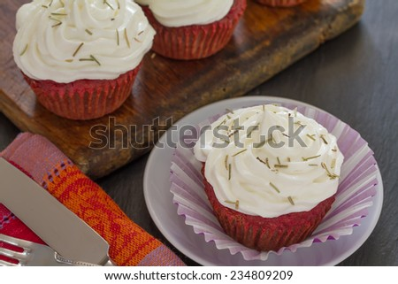 Beetroot velvet cupcakes with goat cheese cream and dried rosemary, close up - stock photo