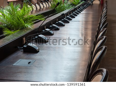 Before a conference table with microphones in front of empty chairs. - stock photo